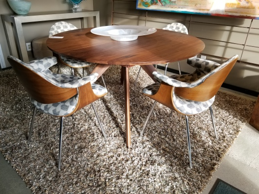 Seams to fit home consignment furniture designer showroom for Round dining table with hidden chairs